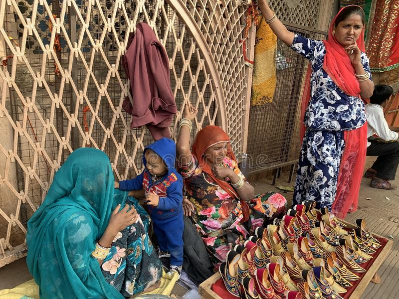 Tribal women are selling traditional colourful shoes for kids royalty free stock photography