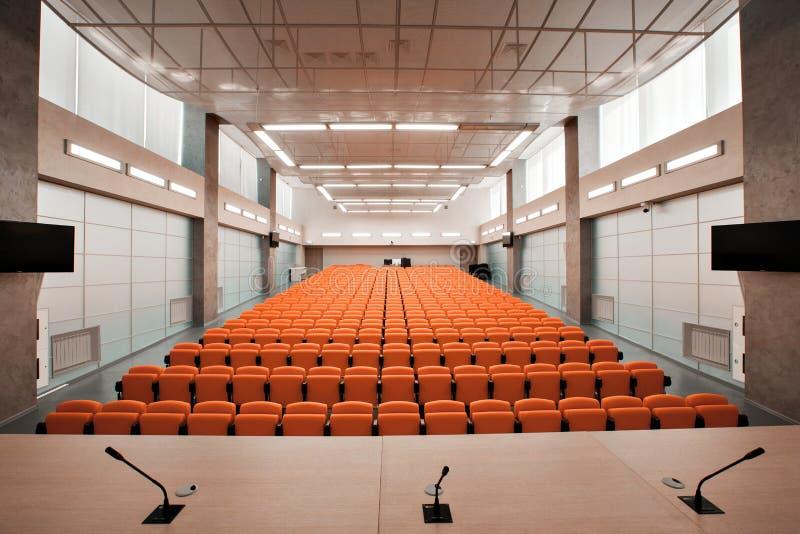 Tribuna com microfone e computador na sala de conferências Cor alaranjada foto de stock royalty free