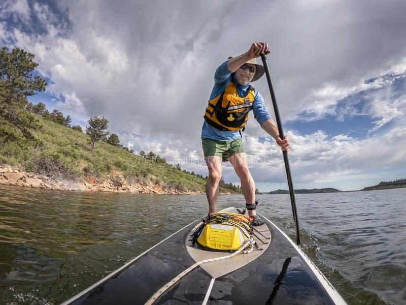 Tribune die omhoog op een meer in Colorado paddelen stock fotografie
