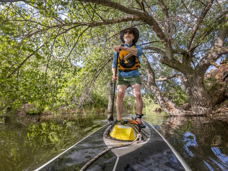 Tribune die omhoog op een meer in Colorado paddelen royalty-vrije stock afbeeldingen