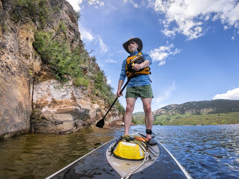 Tribune die omhoog op een meer in Colorado paddelen stock foto