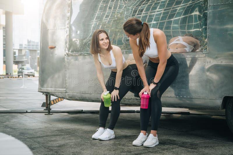 Tribune die van twee drinkt de jonge vrouwenagenten tegen aanhangwagen, rust na opleiding leunen, water, communiceert De meisjes  stock fotografie