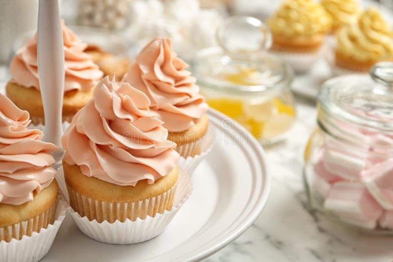Tribune met smakelijke cupcakes op lijst, ruimte voor tekst stock foto