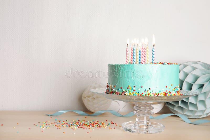 Tribune met verse heerlijke cake en verjaardagsdecoratie op lijst stock afbeelding