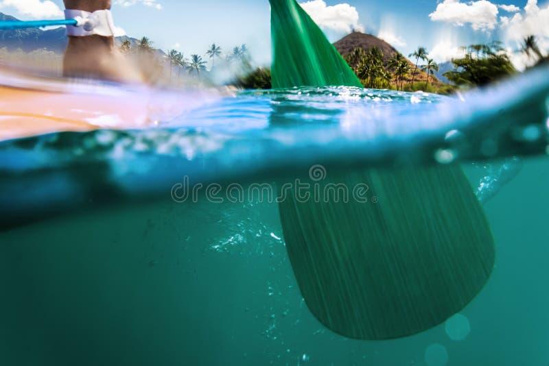 Tribune op peddel het inschepen roeispaan in water stock afbeelding