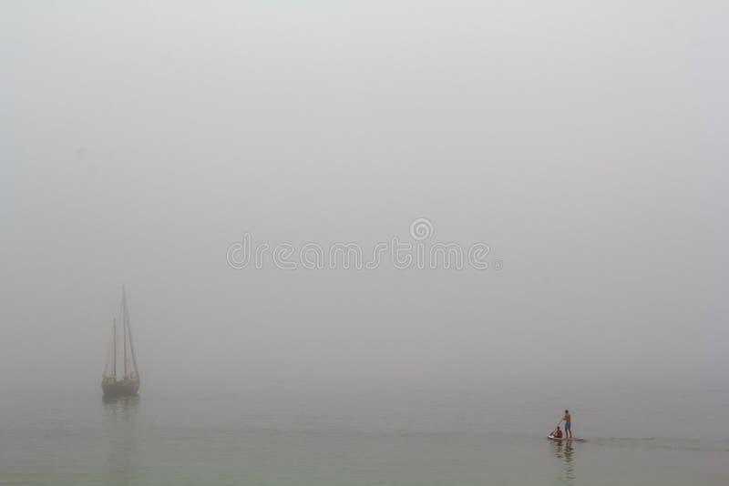 Tribune op peddel het surfen en een varend schip op een stille overzees met mist het omringen stock afbeeldingen