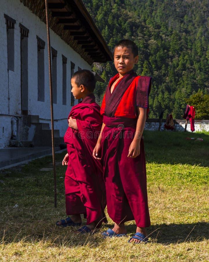 Tribune van twee de jonge beginnersmonniken op het gazon Trashiyangtse Dzong, oostelijke Bhutan royalty-vrije stock foto's