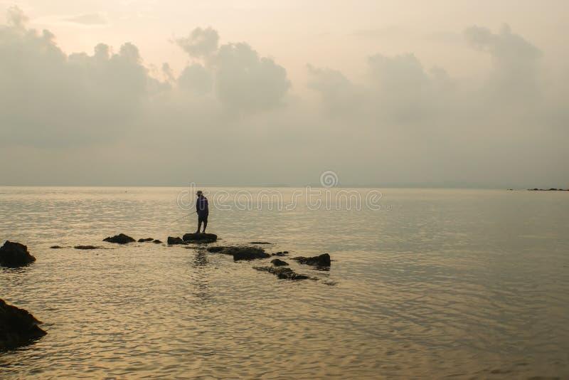 Tribunes van de silhouet de alleen visser op rots op zee kust voor vissenjacht royalty-vrije stock fotografie