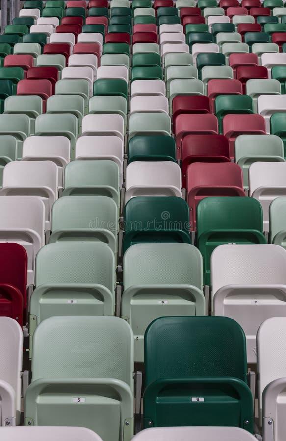 Tribunes vides d'un stade moderne avec des nubers sans spectateurs et des chaises colorées au centre de l'arène photos stock