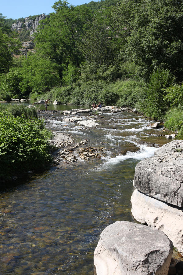 Tributary river in the Ardeche region of France. Rapids and bathers on rocks in the river stock photos