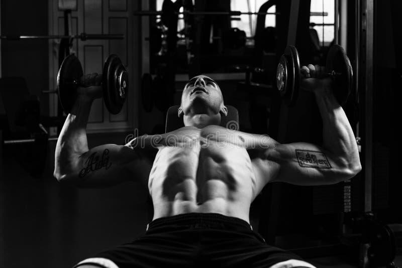 Triceps och bröstkorg för man funktionsduglig med hantlar royaltyfria foton