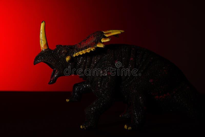 Triceratops med fläckljus på huvudet och röda ljuset på bakgrund royaltyfria bilder