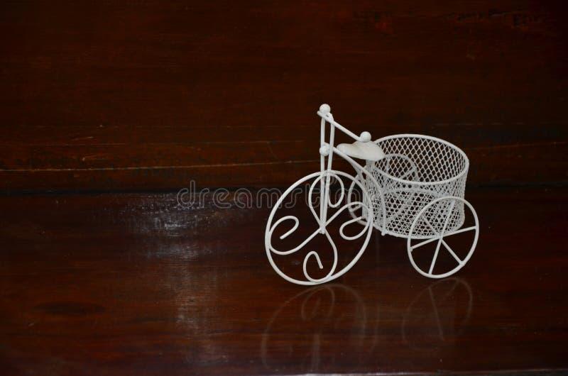 Triciclo bianco per la decorazione sullo scintillare pavimento di legno immagini stock libere da diritti