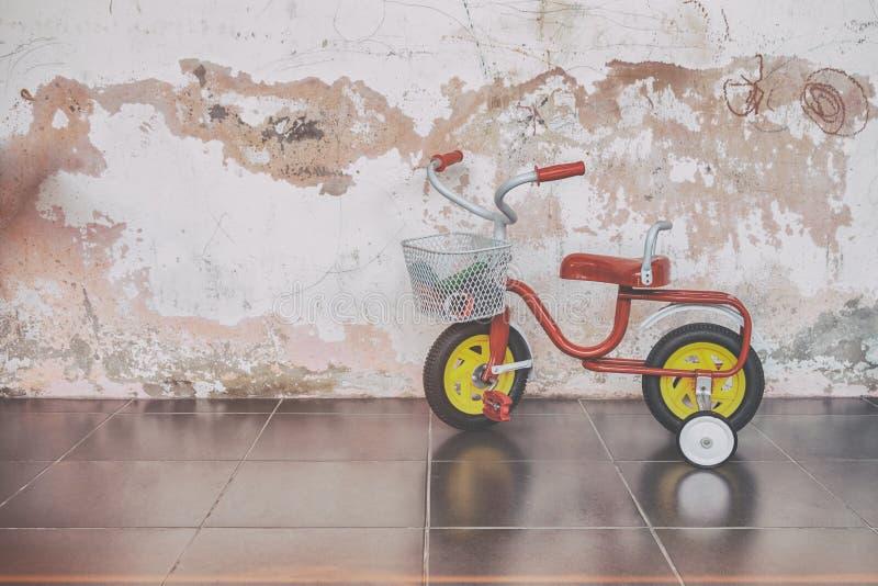 Triciclo de crianças retro na escola do jardim de infância, boas memórias velhas do estilo da infância foto de stock royalty free