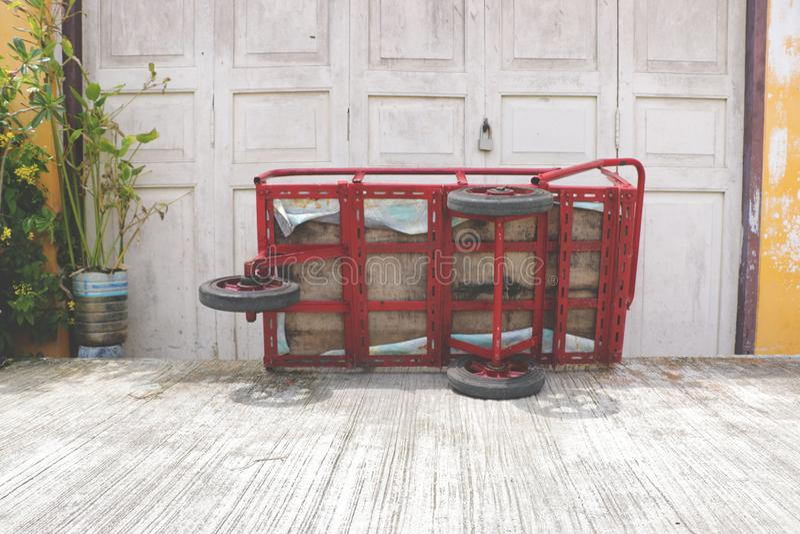Triciclo rosso che si trova dalla parete d'annata immagini stock