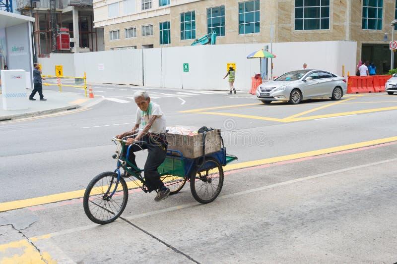 Triciclo Singapore di guida dell'uomo anziano immagini stock libere da diritti