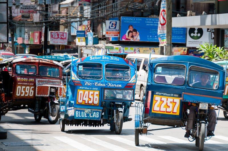Triciclos azuis de Dumaguete que conduzem na estrada imagens de stock