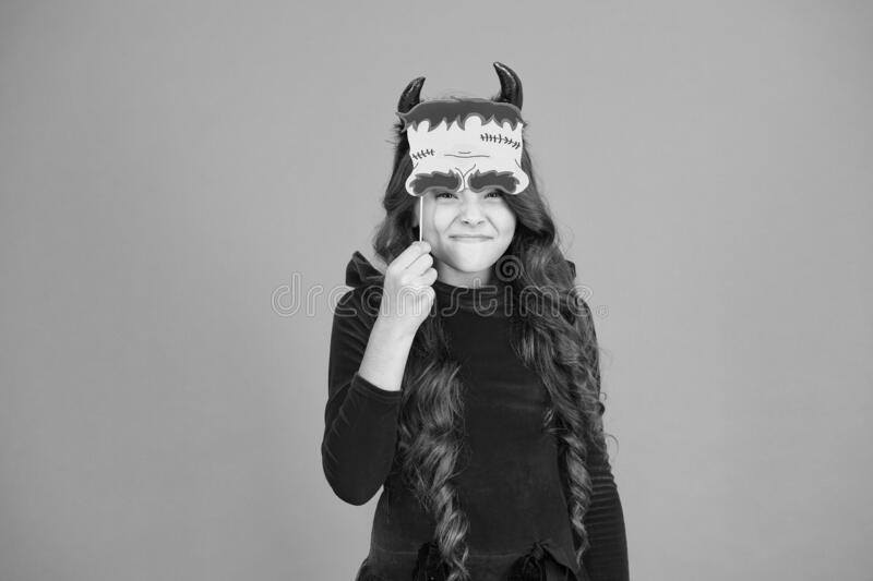 Trick or treat concept. Halloween costumes. Photo booth props. Autumn holiday. Little girl cute small horns celebrate. Halloween. Carnival concept. Small child stock photography