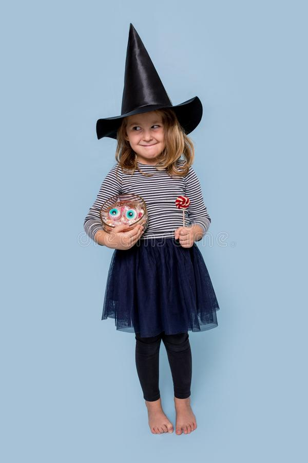 Cute little girl in a witch costume at Halloween holds candy and lollipop royalty free stock photography