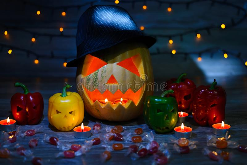 Trick or treat! Favourite autumn holiday. Mystical scary jack-o-lantern in hat and frightening peppers. Sweets, light garland, ca royalty free stock photography