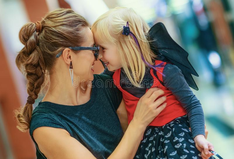 Happy modern mother and daughter on Halloween at mall hugging. Trick or Treat. happy modern mother and daughter in bat costumes on Halloween at the mall hugging stock image