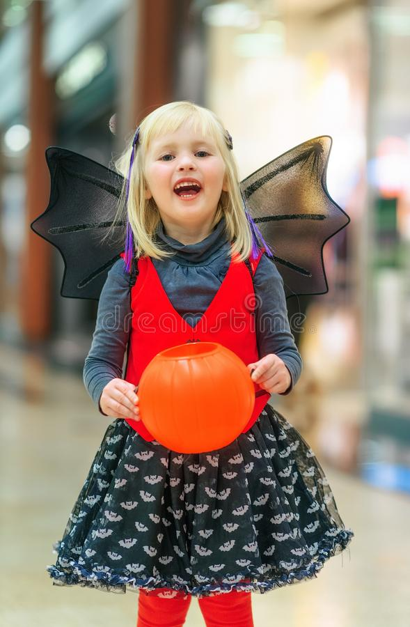 Happy girl with Halloween pumpkin Jack O'Lantern basket. Trick or Treat. Portrait of happy modern girl in bat costume at the mall with Halloween pumpkin royalty free stock photo