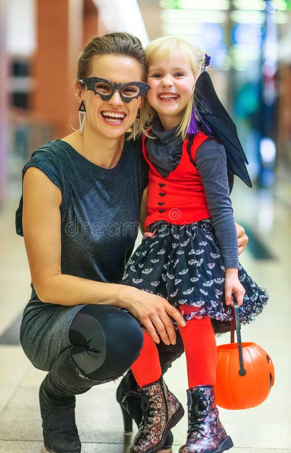 Happy modern mother and child on Halloween at mall. Trick or Treat. Portrait of happy modern mother and child in bat costumes on Halloween at the mall stock photos