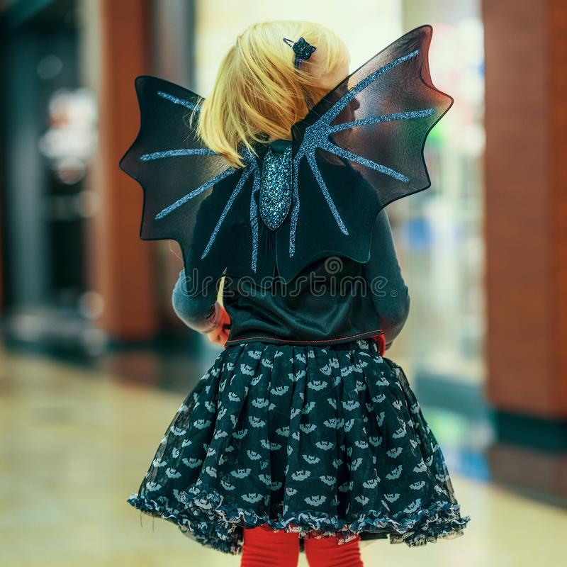 Modern child in bat costume on Halloween at mall stock image