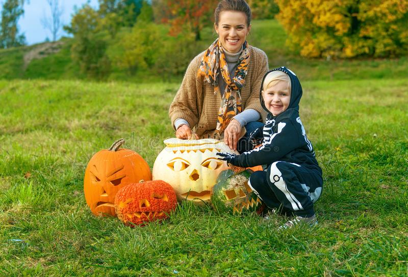 Mother and daughter among Halloween pumpkins Jack O'Lantern royalty free stock photo