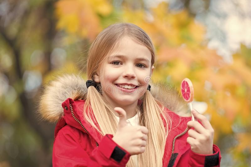 Trick or treat sweet candy. Kid girl wear coat for fall season. Child cheerful eat lollipop candy fall sunny day. Girl stock photos