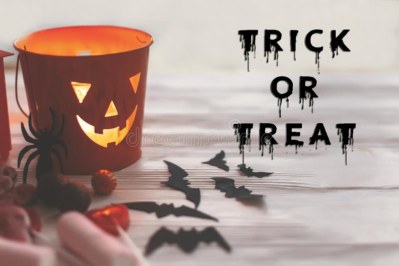 Trick or treat text, bloody sign. Happy Halloween. Jack o Lantern bucket with holiday candy, bats, spiders, skulls on white. Rustic wooden background. Season`s stock photo