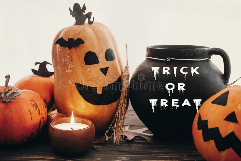 Trick or Treat text, Happy Halloween. Pumpkins, jack-o-lantern,. Witch cauldron, bats, spider, candle, autumn leaves on black wood in light. Halloween royalty free stock photos