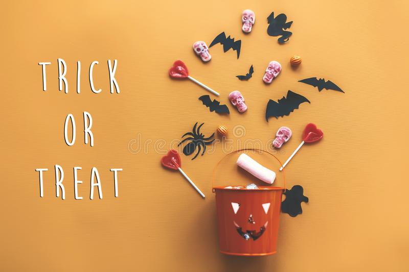 Trick or treat text sign. Happy Halloween. Jack o Lantern bucket. With holiday candy, bats,spiders, skulls on orange paper, flat lay. Space for text. Season`s stock image
