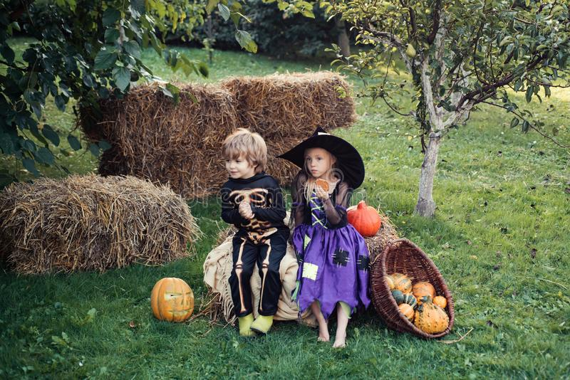 Trick-or-treating. Happy Halloween Cute children daughter and son making funny faces with a pumpkin. Halloween Scene royalty free stock photo