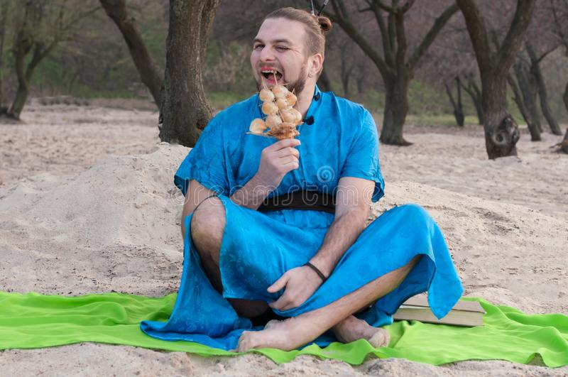 Tricki transsexual handsome man sitting on sand in blue kimono, picking teeth with ship model stock photography