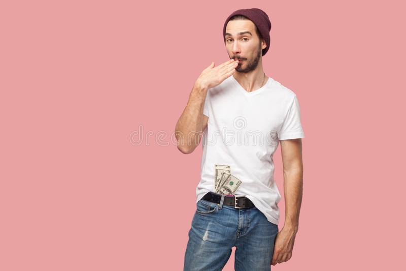 Tricky handsome bearded young hipster man in white shirt and casual hat standing, hold many dollars money on the pocket, with stock photos