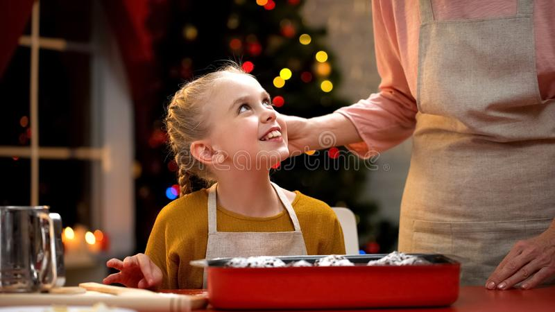 Tricky little girl secretly tasting chocolate muffin, Christmas preparation royalty free stock photos