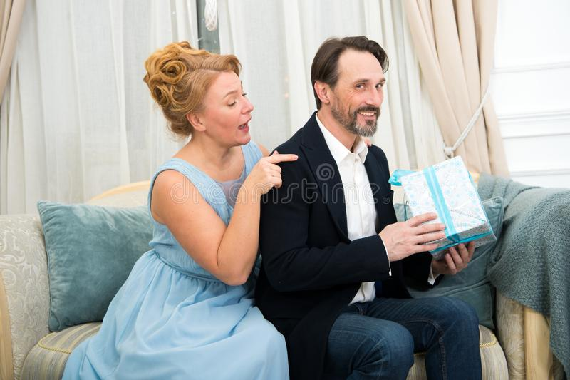 Tricky smiling man keeping birthday present while his wife touching his shoulder and being curious royalty free stock photography