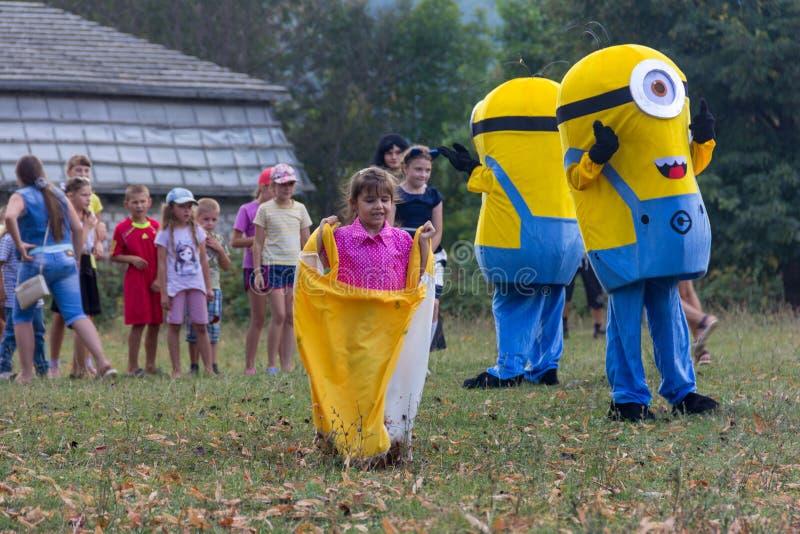 Trickzeichner im Kostüm eines Günstlings, der mit den Kindern am Festtag des Dorfs von Kamennomostskiy in der Herbst Gleichheit s stockbilder