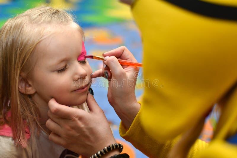 Trickzeichner malt das Gesicht einer Farbe des kleinen Mädchens an einem Feiertag lizenzfreies stockbild