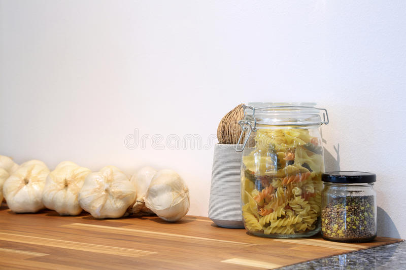 Tricolor spiral pasta and grain in glass jar with giant garlic i royalty free stock images