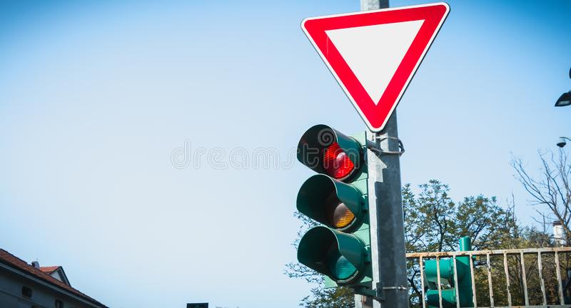 Tricolor traffic light with a triangle sign giving way. In Italy stock photography