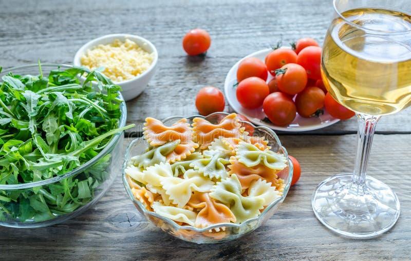 Tricolore farfalle med arugula, parmesan och körsbärsröda tomater royaltyfria foton