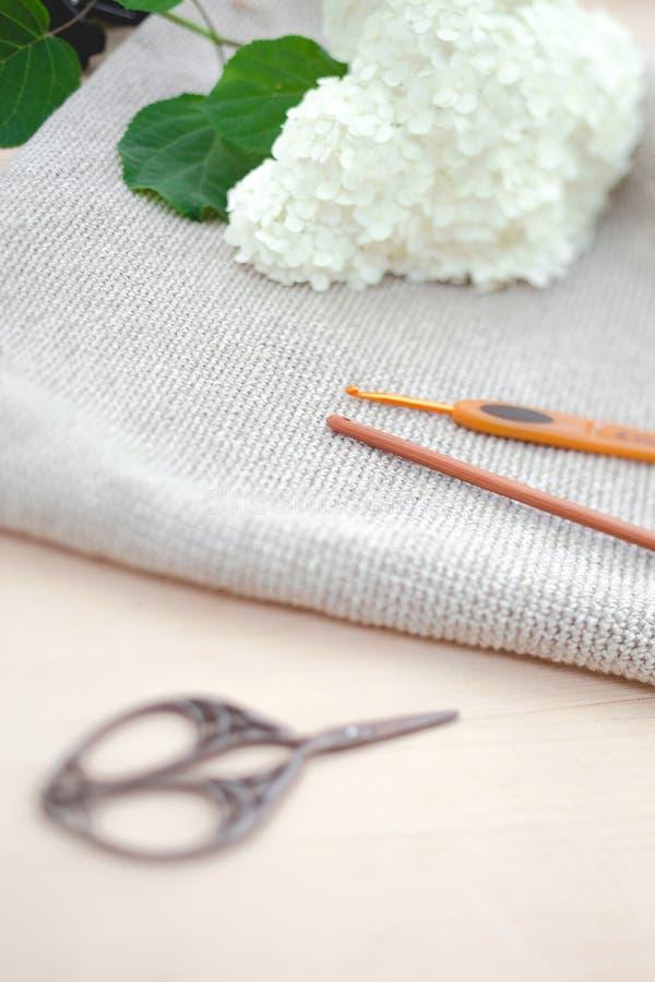 Tricotage comme passe-temps Ciseaux en métal et crochet de crochet en bois pour tricoter et fleurs blanches sur le fond en bois photos libres de droits