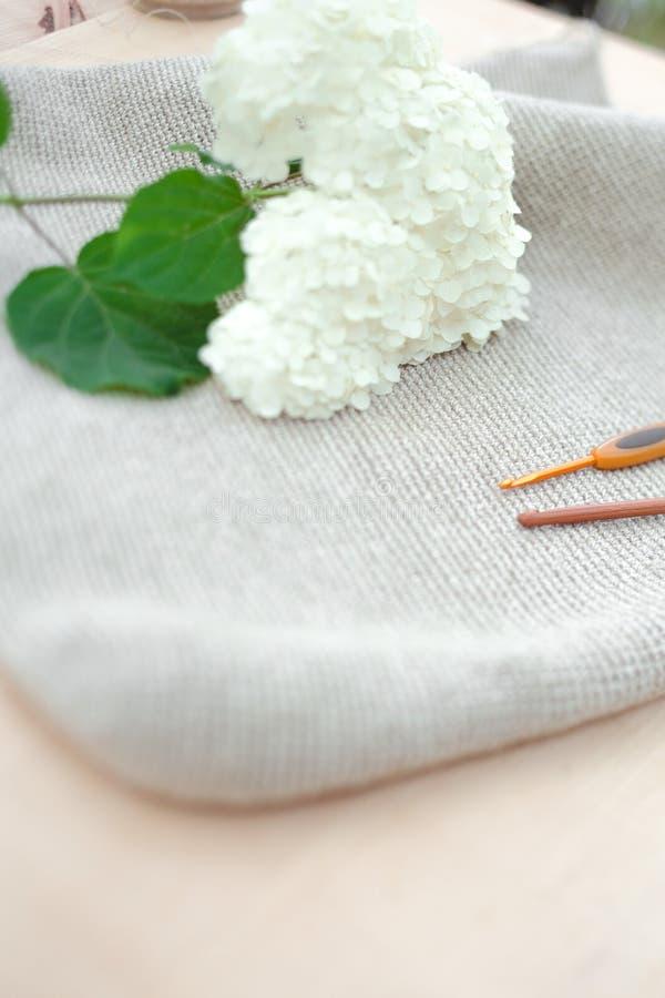 Tricotage comme passe-temps Crochets de crochet en métal et en bois pour tricoter et fleurs blanches sur le fond en bois image stock