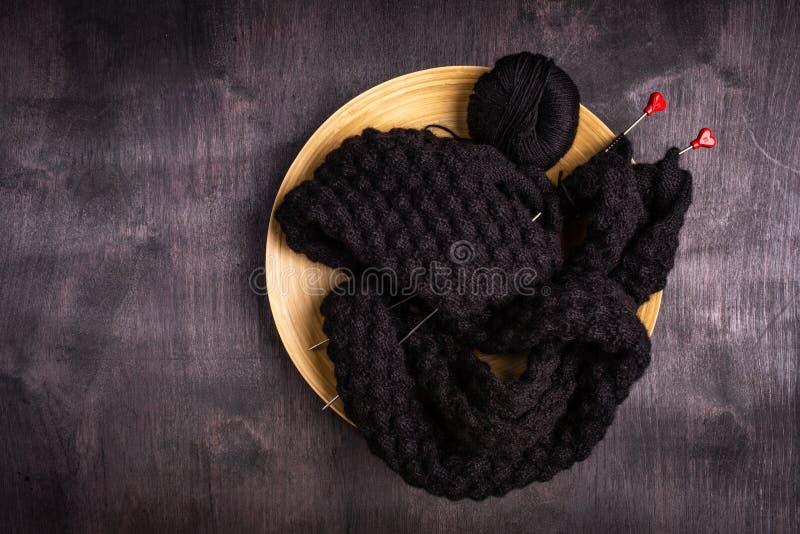 tricotage des fils noirs dans un plat sur un noir et un fond en bois gris photo libre de droits