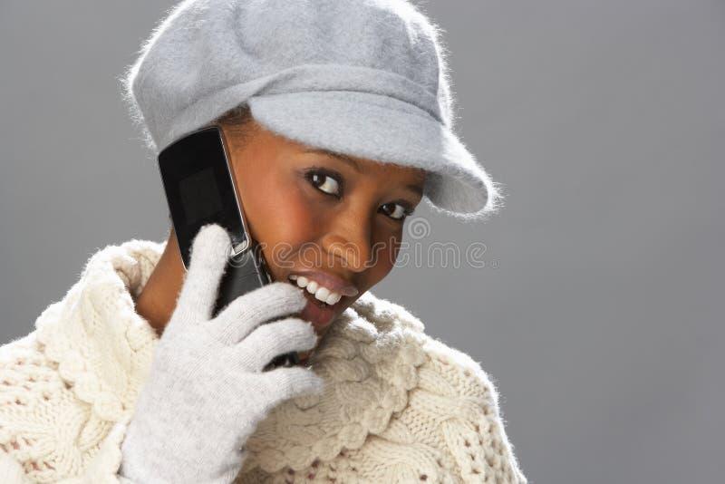 Tricots s'usants de femme dans le studio utilisant le mobile image libre de droits