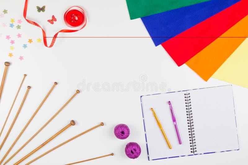 Tricottando, cucendo e lavori all'uncinetto gli strumenti con il taccuino di carta su fondo bianco immagini stock