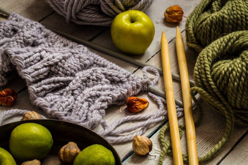 Tricottare lana grigia con le palle su fondo di legno fotografia stock libera da diritti