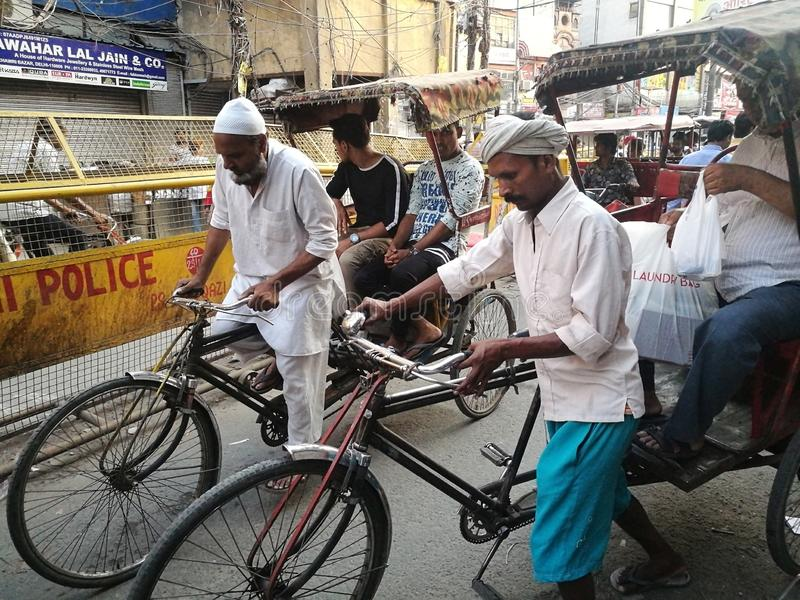 A tricycle driver is having a friendly discussion with his passenger in India. NEW DELHI , INDIA - MAY 19,2019 : Unidentified driver tricycle is taking royalty free stock image